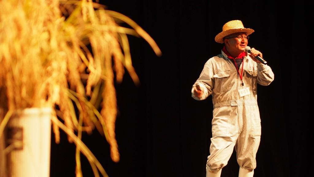 稲を持ち込んで田んぼアートの魅力を伝える市川さん